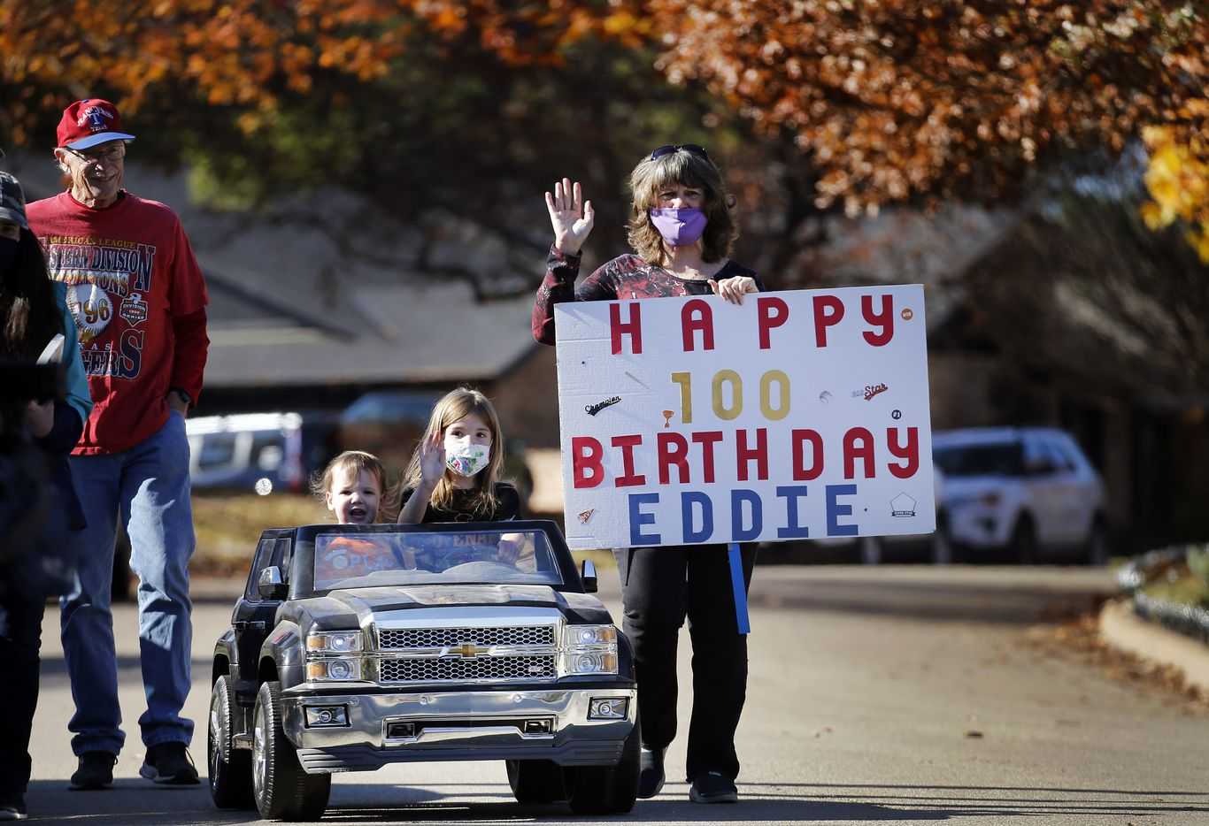 Clayton and Aubrey Myles along with their grandmother Pam Lay (right) drive to Eddie Robinson's early, drvie-thru 100th birthday event.  The oldest living former MLB player will turn 100 on December 15th. To share his birthday with friends, his family orchestrated a drive-by celebration outside his Fort Worth home, Saturday, December 12, 2020. His 65 year career started by playing for the Cleveland Indians and serving in World War II. Later he went on to play for several other teams before presiding over three winning seasons as the Texas Rangers general manager. He is still in great physical health as he waves to passersby, including former teammates, GM Tom Grieve and U.S. congressman and neighbor Marc Veasey. (Tom Fox/The Dallas Morning News)