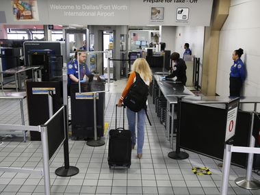 A single passenger makes her way through a TSA security checkpoint at DFW International Airport on Wednesday, April 8, 2020. An agent at this checkpoint, C21, tested positive for COVID-19 after last working April 8 from 12:30 to 9 p.m.. (Vernon Bryant/The Dallas Morning News)