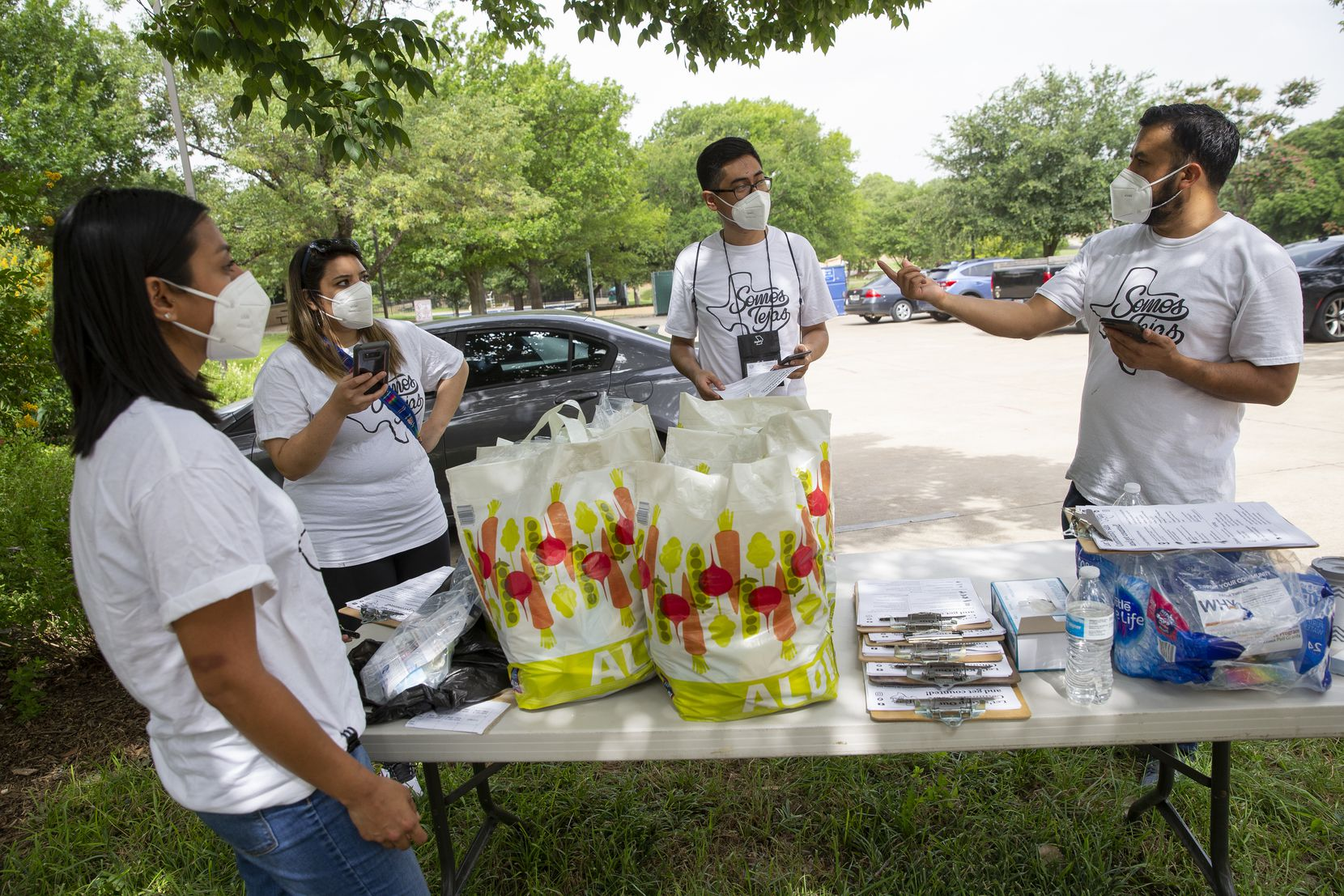 Ramiro Luna-Hinojosa (right) speaks to members of Somos Tejas at Martin Weiss Park before they go door to door in the Oak Cliff neighborhood educating people on COVID-19, the census and voting on June 27, 2020, in Dallas. (Juan Figueroa/The Dallas Morning News)