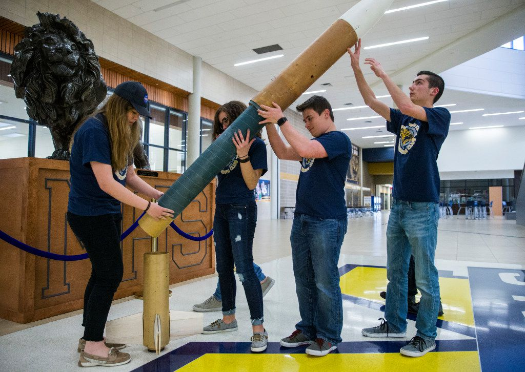 From left: Project manager Kathryn Lehocky, 18, chief of safety Alex Macias, 16, payload B (or drone) engineer Alex Lehocky, 18, and media and mechanical safety ground equipment manager Mitchell Palmer, 16, assemble the McKinney High School Flying Lions Rocketry Club's nearly 10-foot long rocket at McKinney High School. (Ashley Landis/The Dallas Morning News)