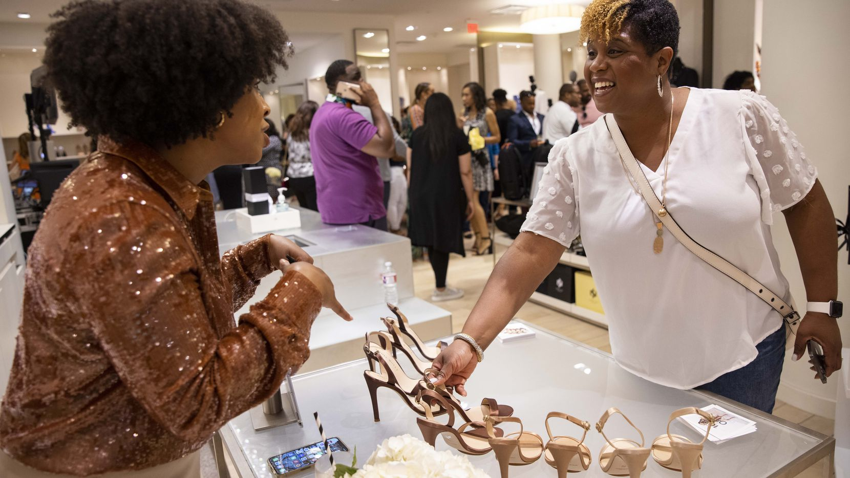Designer Salone Monet, left, talks to customer Judy Garner at the Black Fashion Movement pop-up store on Wednesday.
