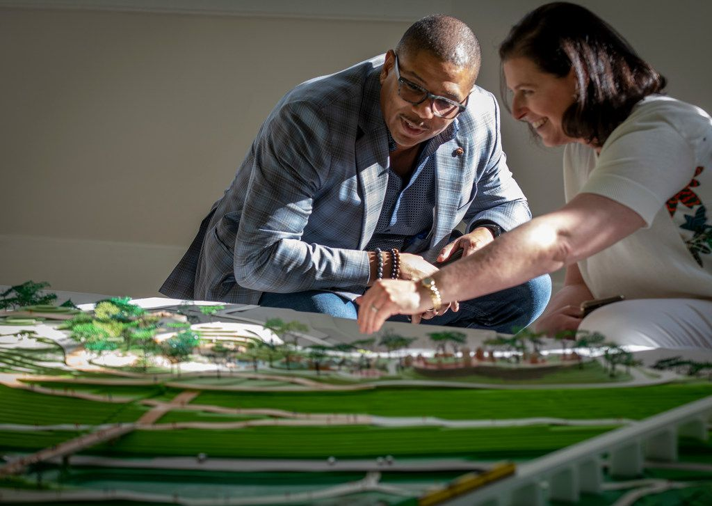 Darren James, a Trinity Park Conservatory board member, left, listens while Elizabeth Silver, a member of the design team, talks while looking at a model of Harold Simmons Park on display at Old Dallas High School in Dallas, Texas on April 25, 2019.