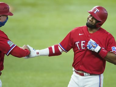Texas Rangers shortstop Elvis Andrus celebrates with first base coach Corey Ragsdale after reaching on a single during the first inning against the Oakland Athletics at Globe Life Field on Saturday, Sept. 12, 2020.