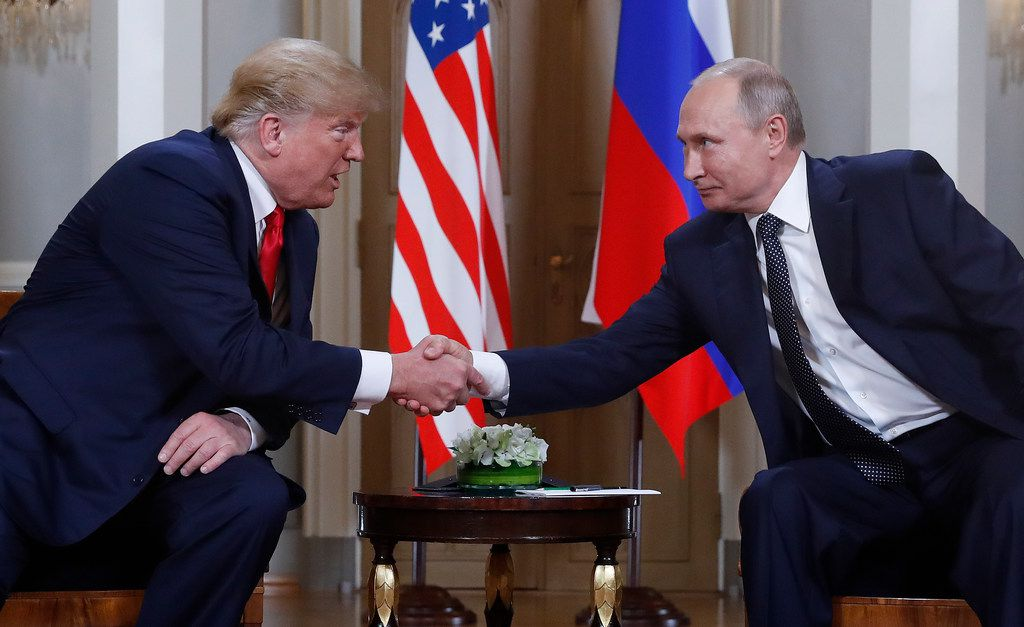 The real U.S. president, Donald Trump (left), shakes hands with Russian President Vladimir Putin during  a meeting at the Presidential Palace in Helsinki earlier in July. A prankster deposited a portrait of Putin near a space reserved for U.S. presidents at the Colorado state capitol building last week.