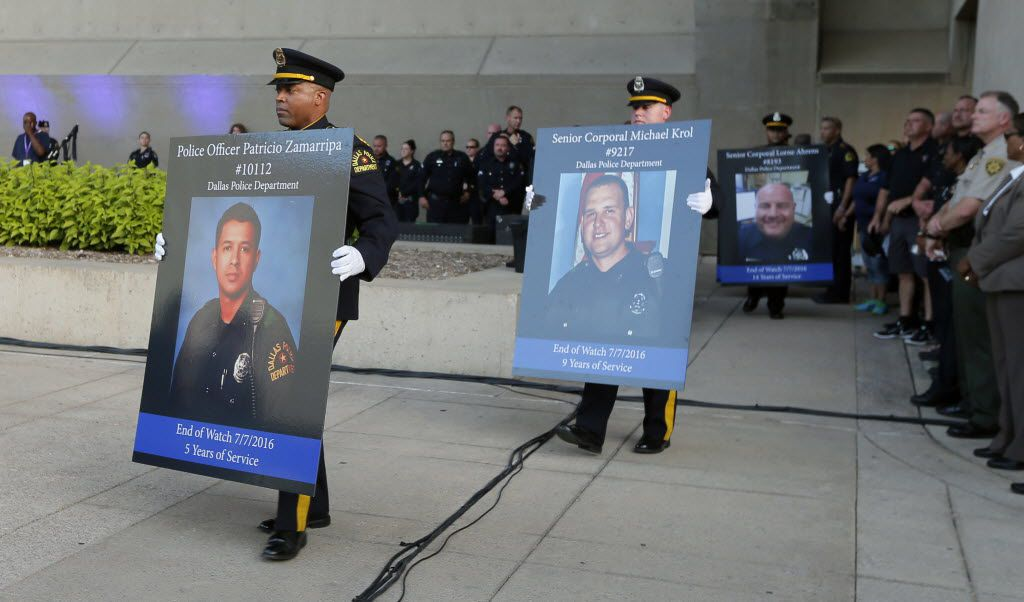 Honor guard carry portraits of fallen officers during a candlelight vigil at City Hall, Monday, July 11, 2016, in Dallas. Five police officers were killed and several injured during a shooting in downtown Dallas last Thursday night. (AP Photo/Tony Gutierrez)