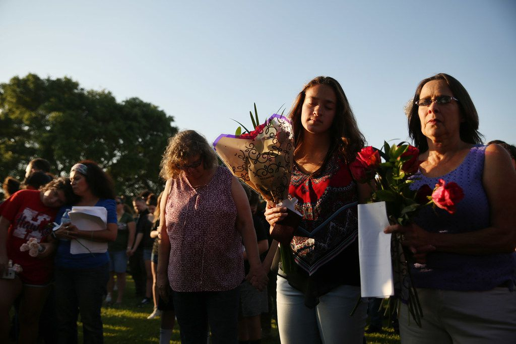 "Mourners pray during a vigil after the shooting at Santa Fe High School in Santa Fe, Texas. ""We need to do more than just pray for the victims and their families,"" Gov. Greg Abbott said Friday. ""It's time in Texas ... to make sure this tragedy is never repeated."""