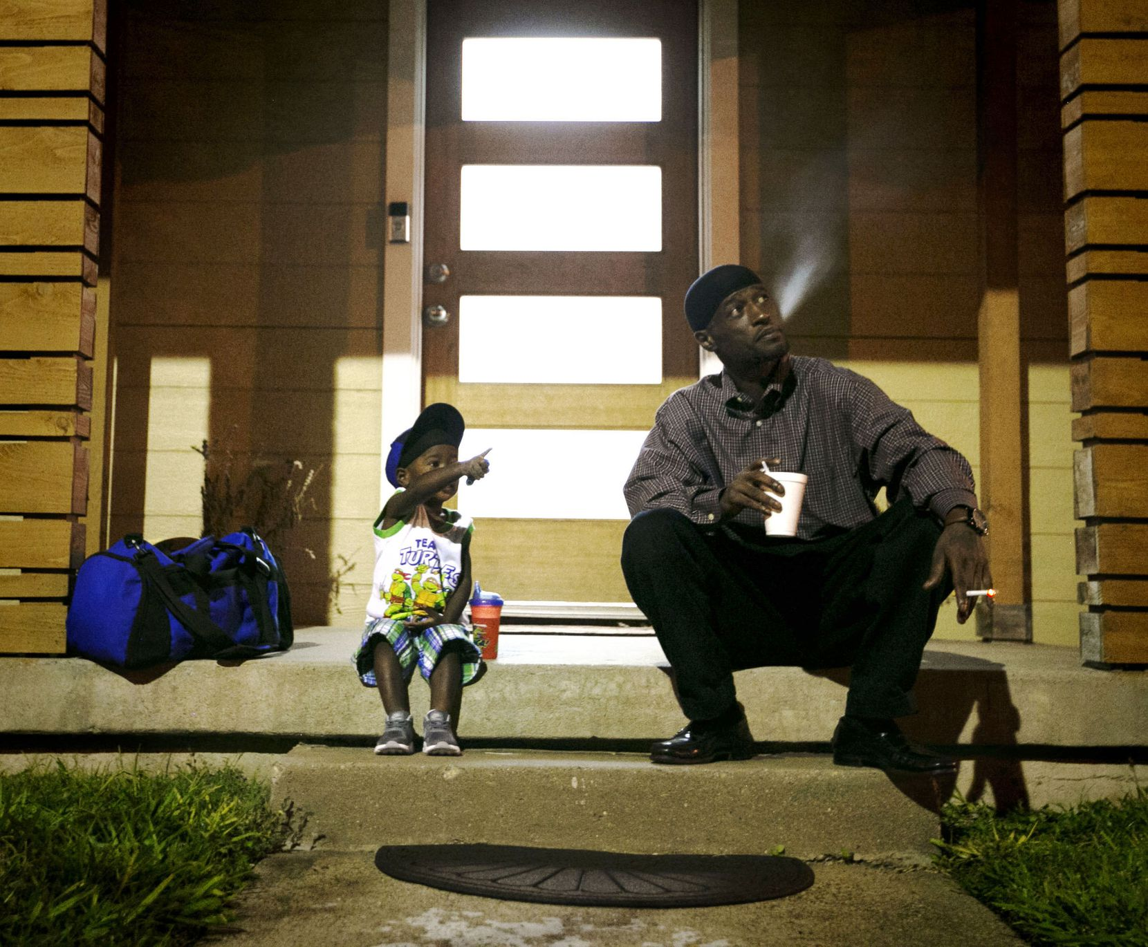 Joshua Miller and his son, Jordan, wait for the day care van to arrive.
