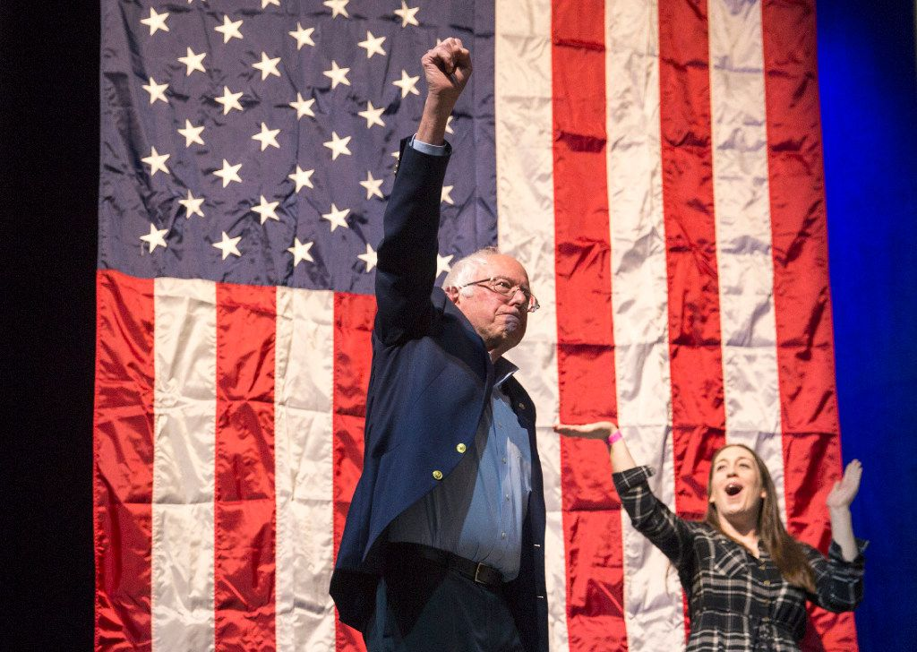 """In this April 17, 2017 photo former presidential candidate Bernie Sanders greets the crowd at a packed State Theatre before his speech at the """"Come Together and Fight Back"""" tour in Portland, Maine. Sanders called for a radical transformation of the Democratic Party into a grassroots movement founded on the tenets of his unsuccessful Democratic presidential campaign: fighting against the billionaire class and rigged economic and political systems. (Brianna Soukup/Portland Press Herald via AP)"""