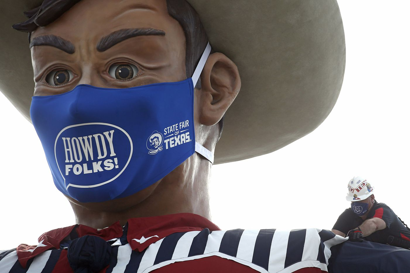David Russ works on the shirt of Big Tex after removing a cable used to hoist him up for installed at Fair Park in Dallas on Tuesday, September 16, 2020. The mask is 84 inches by 45 inches or roughly 7 feet by 4 feet. The State Fair of Texas has been cancelled this year due to the global pandemic.