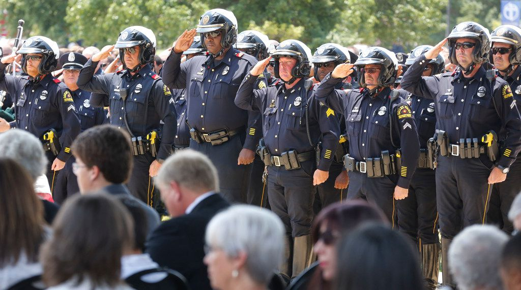 """Dallas motorcycle police officers salute at the funeral service for Dallas Police Department Senior Cpl Earl James """"Jamie"""" Givens, held at Prestonwood Baptist Church in Plano, Texas on Thursday, July 26, 2018. (Louis DeLuca/The Dallas Morning News)"""
