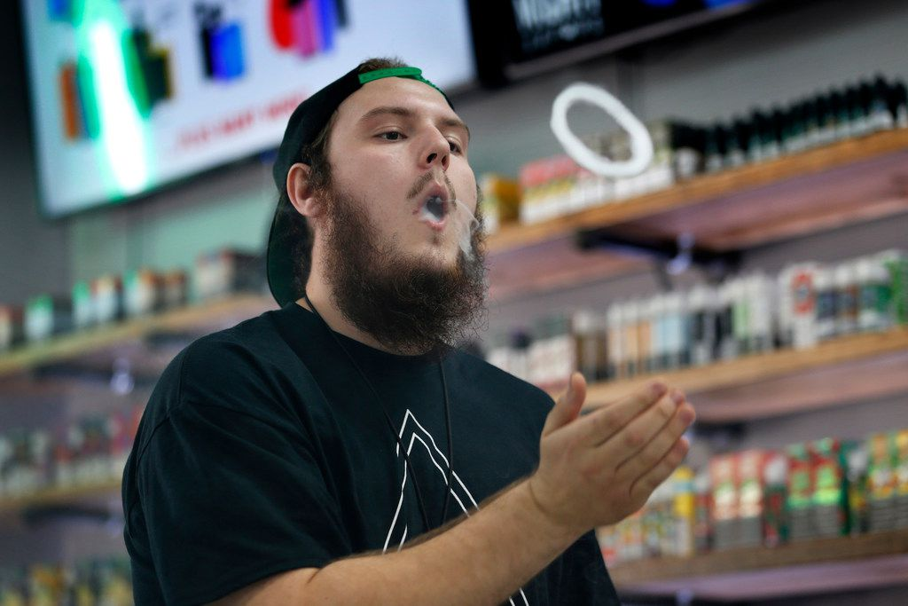 In this Sept. 3, 2019, photo, Devin Lambert, the manager at Good Guys Vape Shop, demonstrates how to blow a vapor ring while using an e-cigarette in Biddeford, Maine.