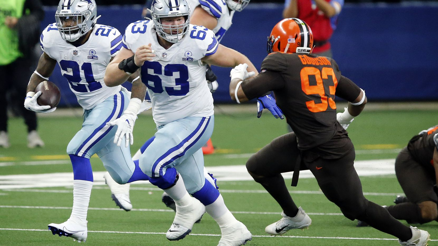 Dallas Cowboys running back Ezekiel Elliott (21) gets a lead block by center Tyler Biadasz (63) on Cleveland Browns middle linebacker B.J. Goodson (93) during the first quarter at AT&T Stadium in Arlington, Texas, Sunday, October 4, 2020.
