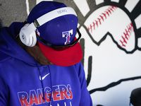 FILE - Rangers hitting coach Luis Ortiz is pictured in the dugout before a spring training game against the Cincinnati Reds at Goodyear Ballpark on Monday, Feb. 24, 2020, in Goodyear, Ariz.