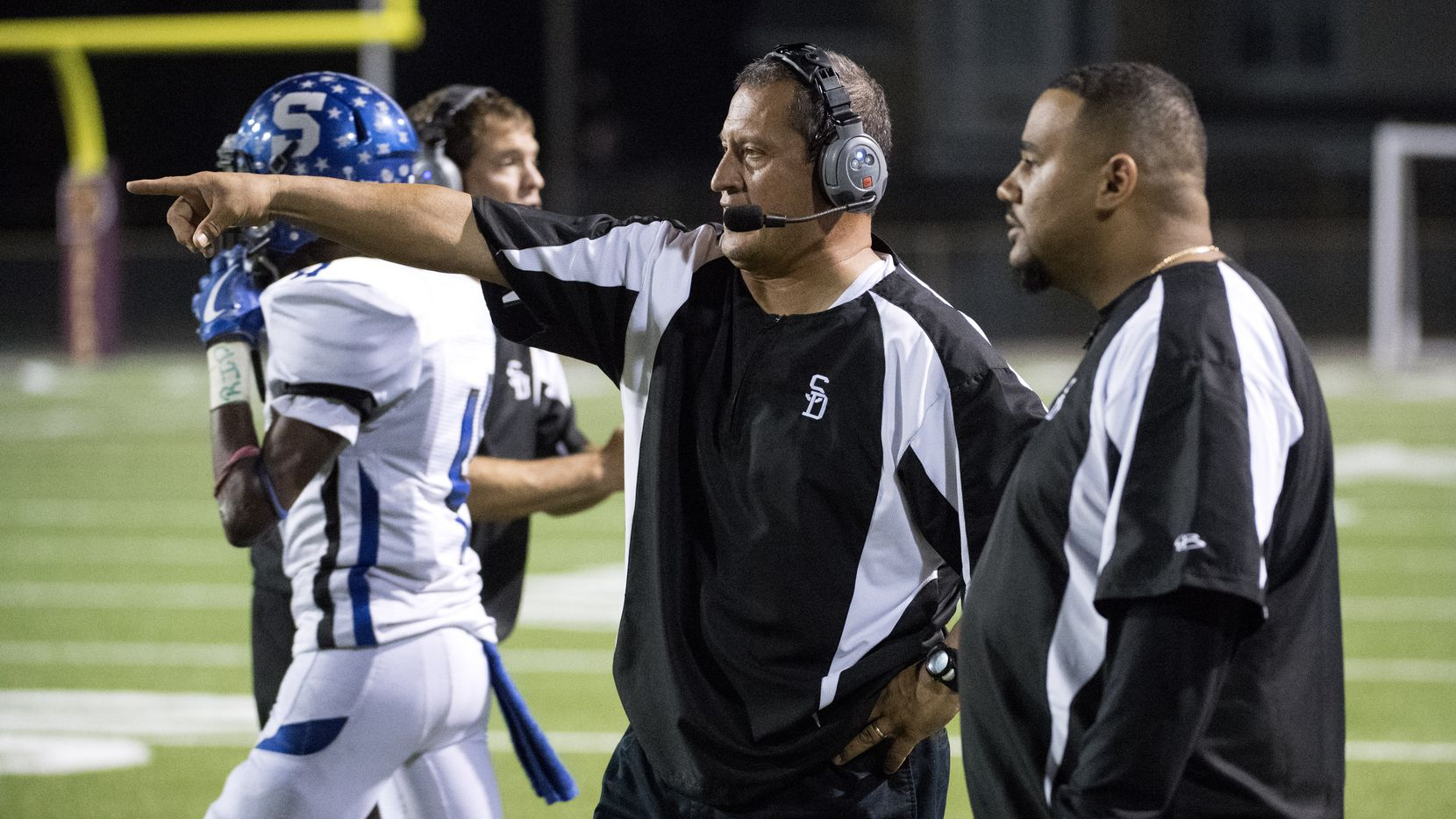 Seagoville head coach Andy Gutierrez confers with another coach during the second half of a high school football game against Bryan Adams on Friday, October 13, 2017 at Forester Field Dallas.