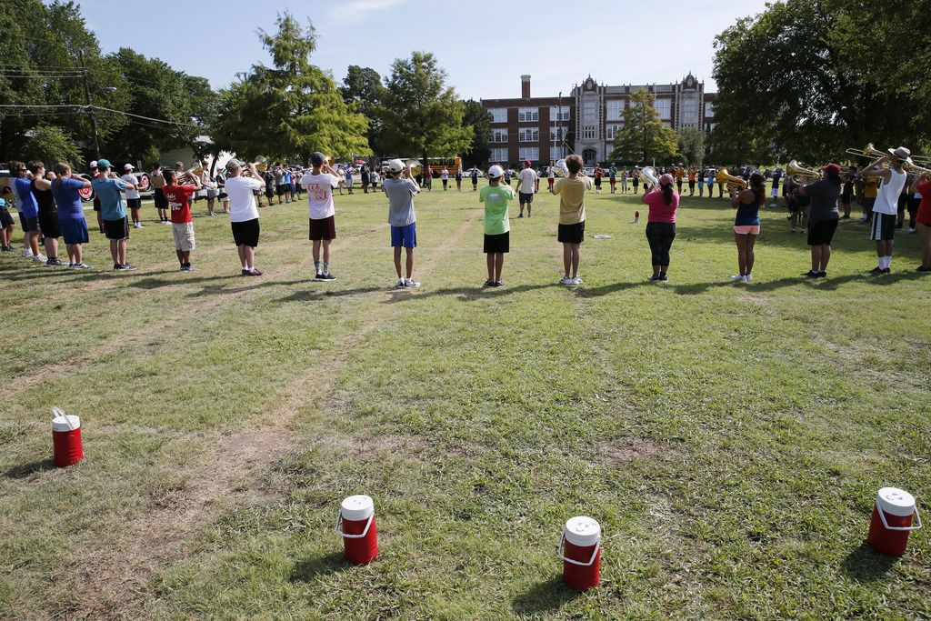 The Woodrow Wildcat Band goes through drills on its practice field across the street from the historic East Dallas campus as part of its two-a-day August camp.