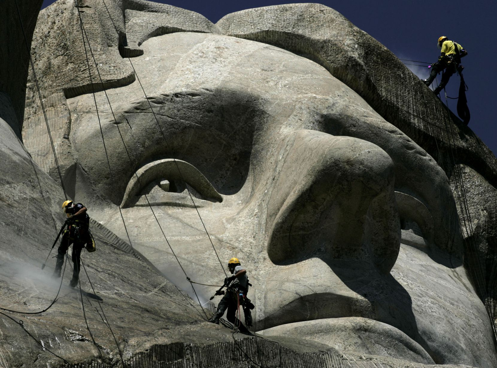 German workers Gerhard Buchar, right, and Winfried Hagenau, left, along with National Park Service employee Darin Oestman use pressure washers to clean around the face of Thomas Jefferson July 22, 2005, at Mount Rushmore National Memorial in South Dakota. The workers are taking part in a project to clean dirt and a fungus called lichen from the monument. The granite sculptures hadn't been washed since they were completed 65 years ago by sculptor Gutzon Borglum.