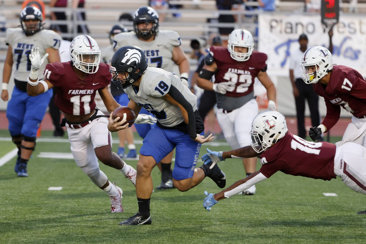 Plane West quarterback Vance Feuerbacher  (19) tries to run past Lewisville defenders Billy Sanford III (11) and Jalen Piece (10) during the first half of a high school football game in Lewisville, Texas on Friday, Sept. 24, 2021. (Michael Ainsworth/Special Contributor)