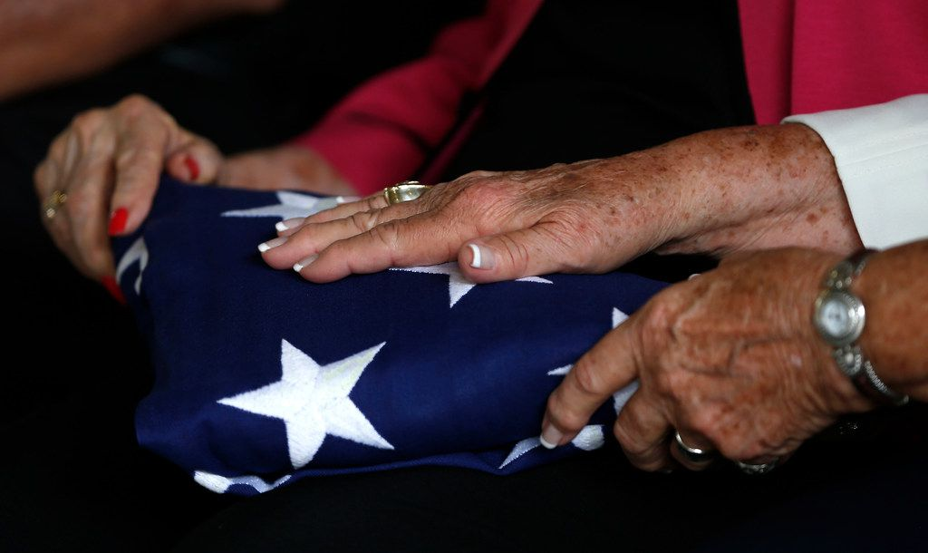 Betty Farris Droby and Judith Bingham, sisters of Army Pvt. Kenneth D. Farris killed during World War II in Germany, rub an American flag that has wrapped over a casket of Pvt. Farris during a burial ceremony at Dallas-Forth Worth National Cemetery in Dallas, Monday, July 9, 2018. Pvt. Farris has his remains identified on April 23, 2018. (Jae S. Lee/The Dallas Morning News)