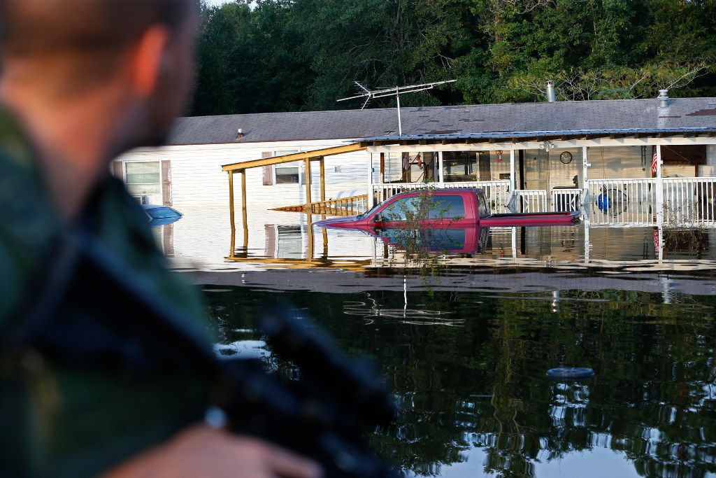 Josh Lambert (left) from the Texas State Rescue Divers (volunteer) provides security on an airboat after Hurricane Harvey in Vidor, Texas, on Sept. 3, 2017.