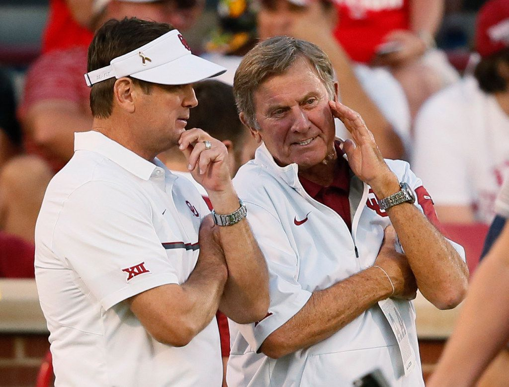 Oklahoma coach Bob Stoops, talks with former Florida coach Steve Spurrier before an NCAA college football game between Ohio State and Oklahoma in Norman, Okla., Saturday, Sept. 17, 2016. (AP Photo/Sue Ogrocki)