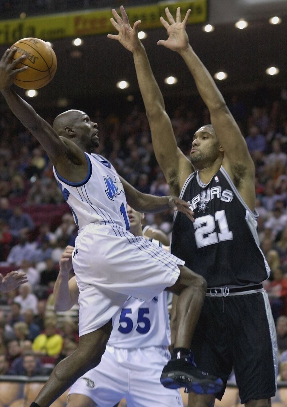 Orlando Magic's Darrell Armstrong (left) drives toward the outstretched arms of San Antonio Spurs' Tim Duncan during the first quarter in Orlando, Fla., on Tuesday, Jan. 9, 2001. Armstrong passed the ball off rather than going for the basket.