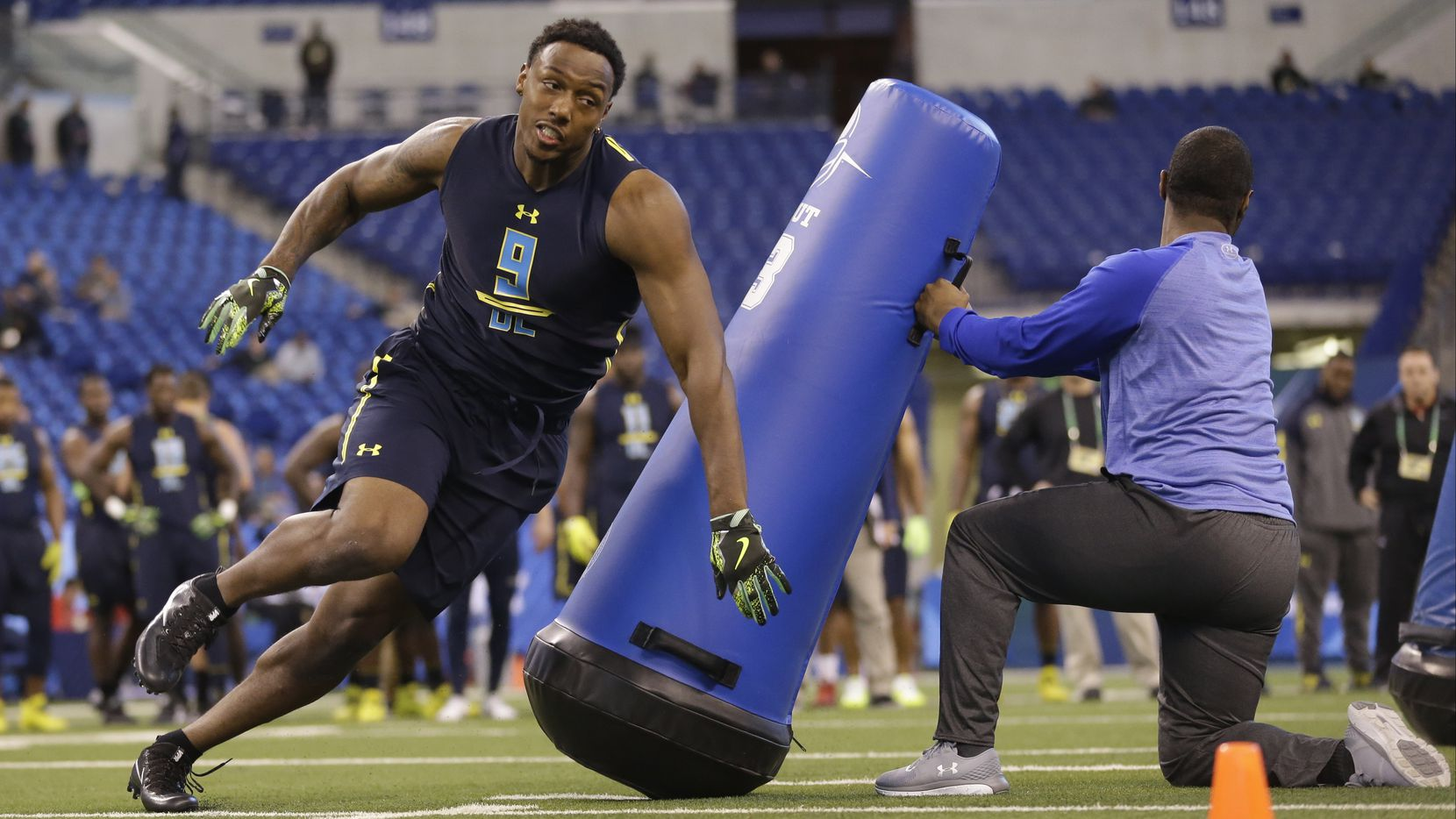 Michigan defensive end Taco Charlton runs a drill at the NFL football scouting combine in Indianapolis, Sunday, March 5, 2017. (AP Photo/Michael Conroy)