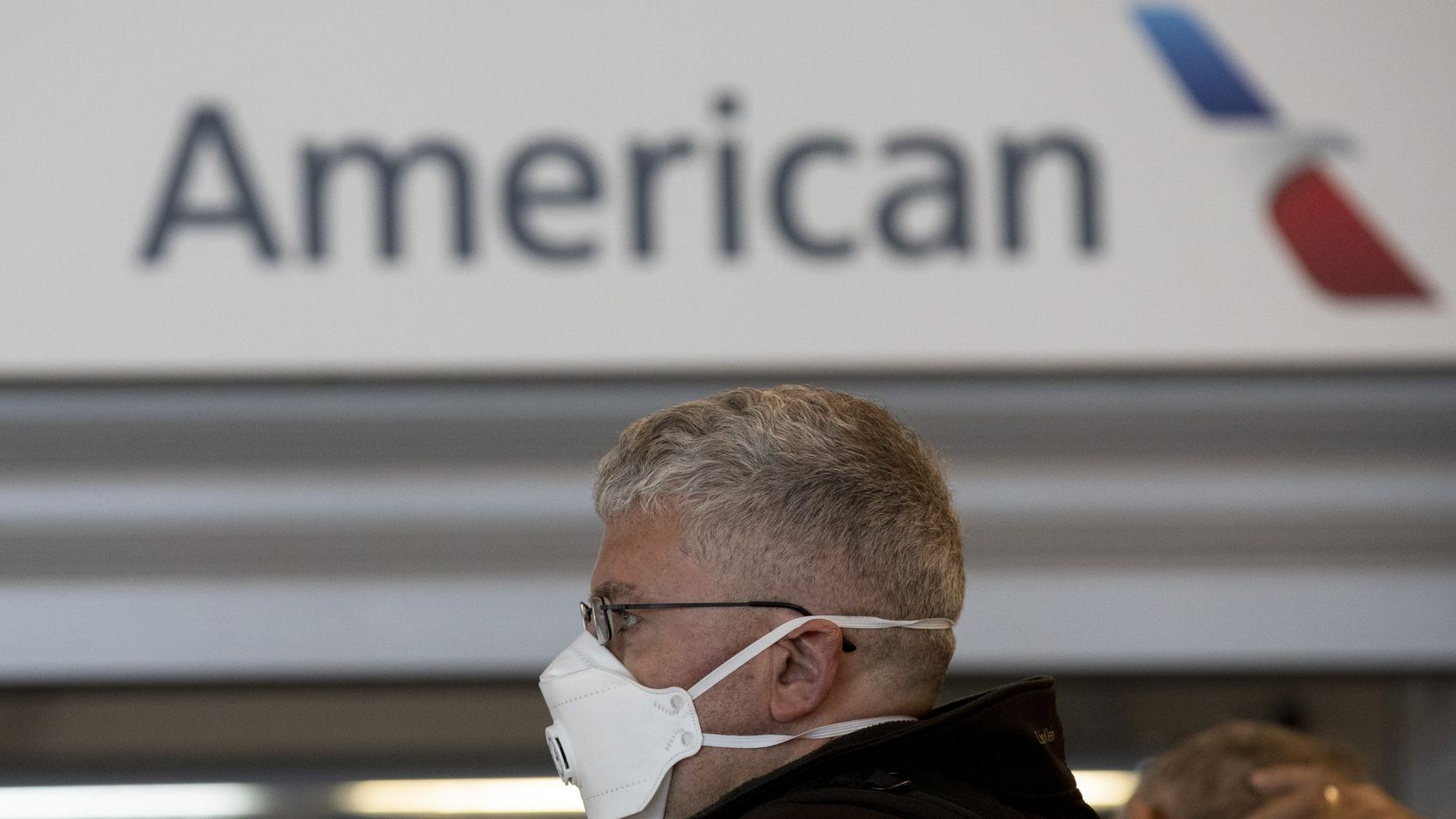 MADRID, SPAIN - MARCH 13: A passenger wearing protective mask queue at customer assistance of American Airlines before the Trump European travel ban goes into effect tonight at Madrid-Barajas Adolfo Suarez Airport on March 13, 2020 in Madrid, Spain. The Trump administration is banning temporarily for 30 days all non-U.S. citizens from flying from continental Europe to the United States in an effort to slow the ongoing spread of the COVID-19. (Photo by Pablo Blazquez Dominguez/Getty Images)