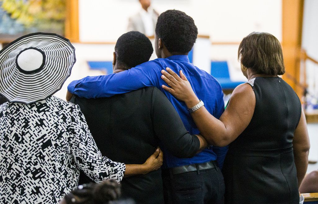 Congregants put their arms around Allison Jean (second from left) and her son, Brandt Jean, during Sunday's prayer service at Dallas West Church of Christ for Botham Jean, who was fatally shot in his own apartment Thursday by a Dallas police officer.