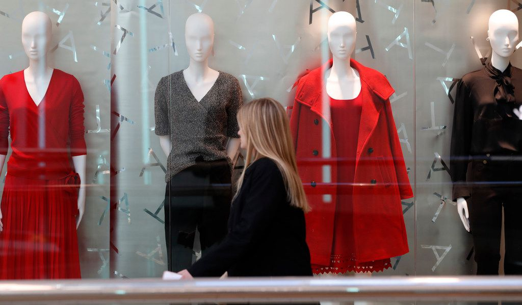 A woman walks by mannequins at the Cherry Creek Mall in Denver on Christmas Eve
