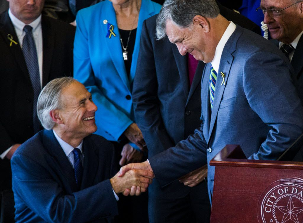 Texas Governor Greg Abbott (front, left) and Dallas Mayor Mike Rawlings (front, right) shake hands after speaking during a press conference on Friday, July 8, 2017 at Dallas City Hall in downtown Dallas, Texas. They stood in front of a group of Dallas city councilmen, state representatives, state senators and Texas Attorney General Ken Paxton. They made comments about a shooting on Thursday, July 7, 2016 in downtown Dallas that targeted police officers and left five people dead and seven more injured. (Ashley Landis/The Dallas Morning News)
