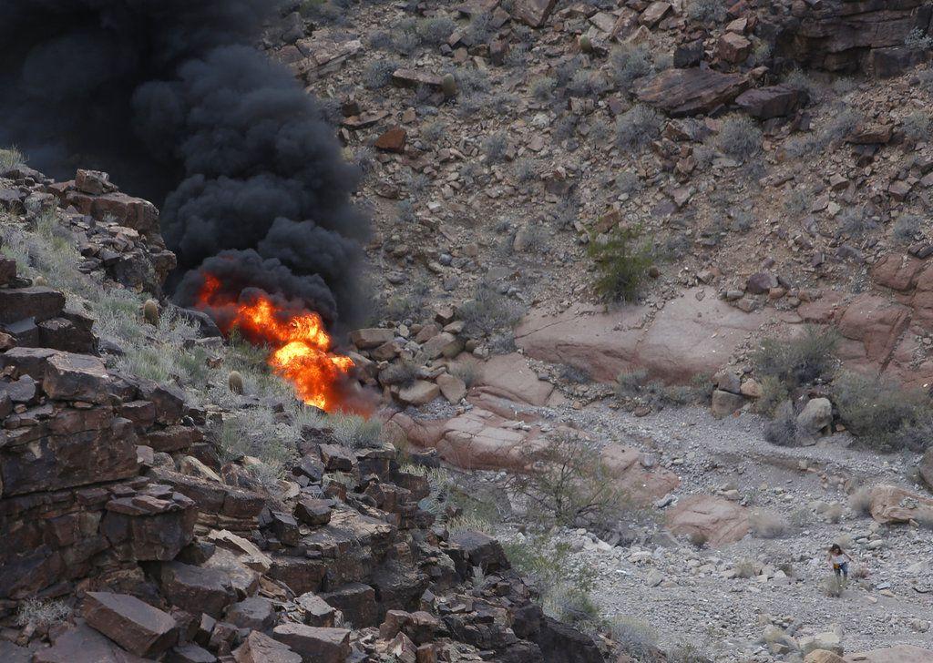 En esta fotografía del sábado 10 de febrero de 2018, una sobreviviente, abajo a la derecha, se aleja del lugar donde se estrelló un helicóptero de turismo en el Gran Cañón en Arizona. Tres personas murieron y cuatro sobrevivieron en el desastre aeronáutico, dijeron las autoridades el domingo. (Teddy Fujimoto vía AP)