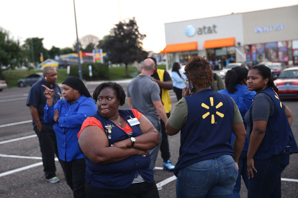 Walmart employees gather in the parking lot after a reported shooting at a store in Wyncote, Pa., near Philadelphia, on Tuesday, Aug. 14.