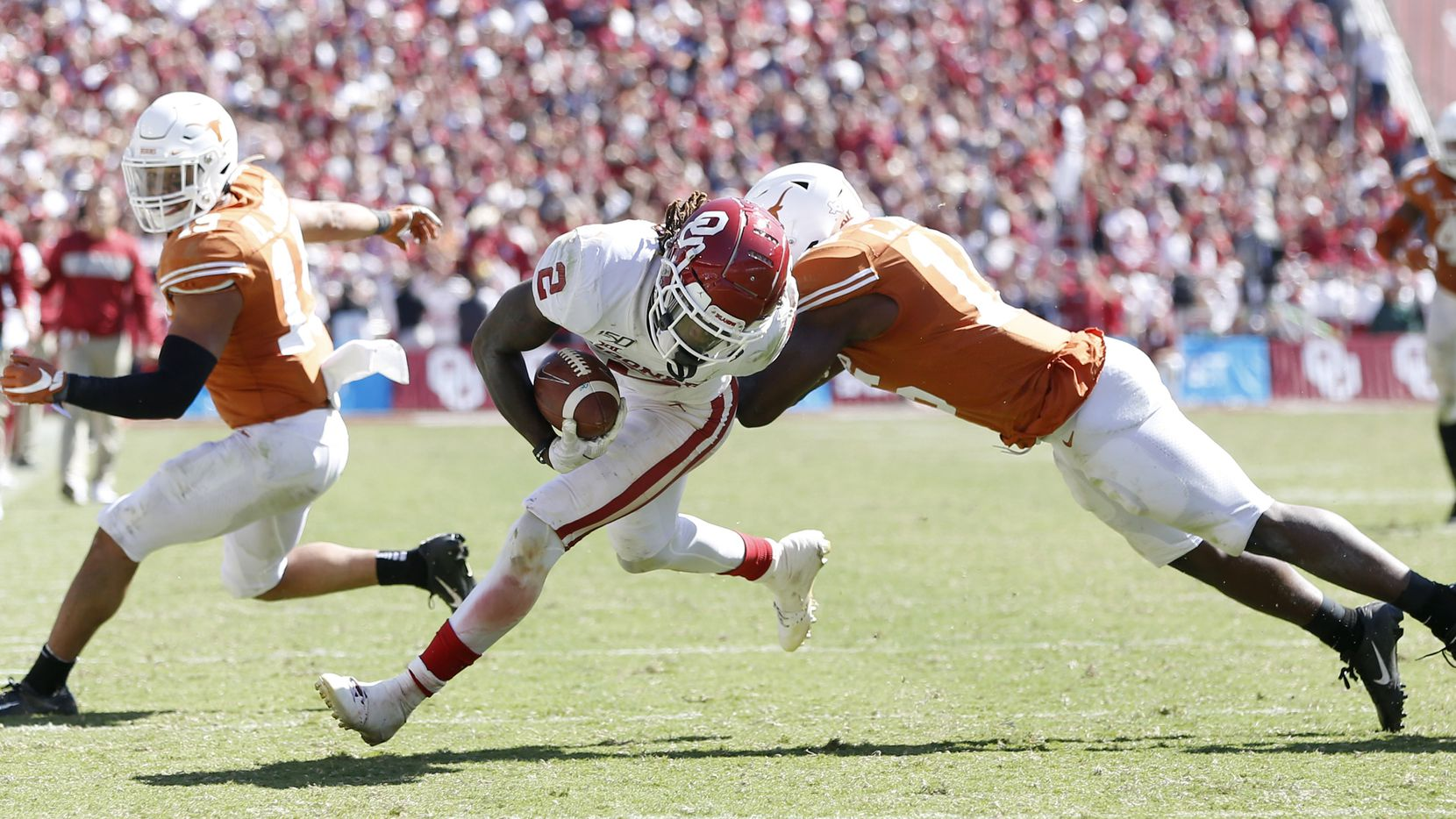 Oklahoma Sooners wide receiver CeeDee Lamb (2) breaks away from Texas Longhorns defensive back Brandon Jones (19) and Texas Longhorns defensive back Chris Brown (15) before scoring a touchdown during the second half of play in the Red River Showdown at the Cotton Bowl in Dallas on Saturday, October 12, 2019. Oklahoma Sooners defeated Texas Longhorns 34-27.