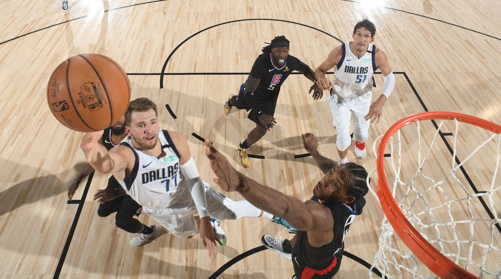 Los Angeles Clippers' Kawhi Leonard (2) fouls Dallas Mavericks' Luka Doncic (77) during the second half of an NBA first round playoff game Sunday, Aug. 30, 2020, in Lake Buena Vista, Fla.