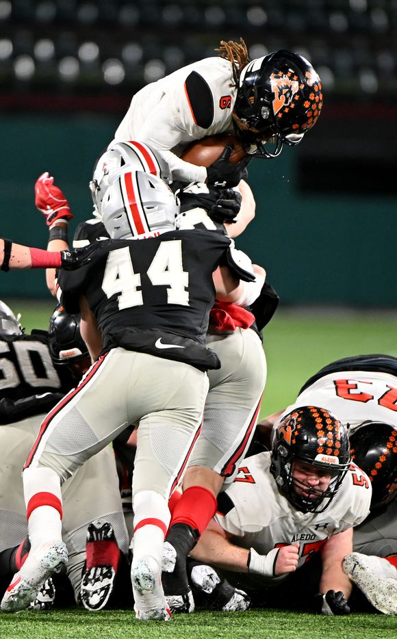 Aledo's Demarco Roberts leaps over Lovejoy's Blake Slaughter for a first down in the second half of the Class 5A Division II Region II final high school football game between Aledo and Lovejoy, Friday, Jan. 1, 2021, in Arlington, Texas. Aledo won 52-48. (Matt Strasen/Special Contributor)