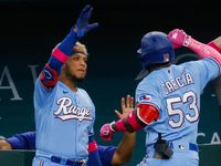 Texas Rangers right fielder Adolis Garcia (53) celebrates in the dugout after hitting a homer to left center against the Seattle Mariners at bottom of the fifth at Globe Life Field on Sunday, May 9, 2021, in Arlington. Texas Rangers second baseman Nick Solak (15) and Texas Rangers first baseman Nate Lowe (30) scored on the hit. The Rangers won, 10-2.