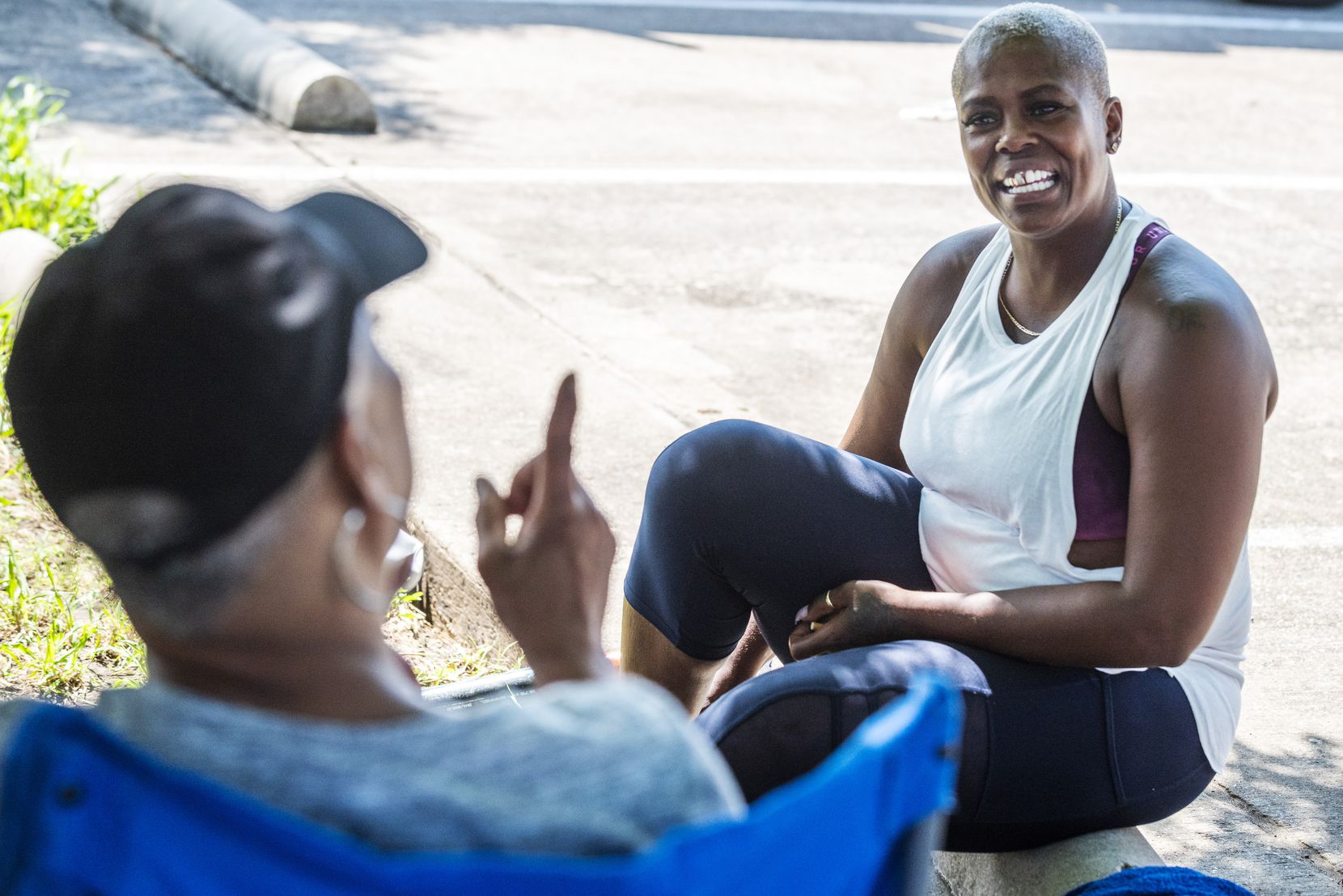 Kyna Bradford, 44 (right), visits in between rounds of a softball tournament at Kiest Park.