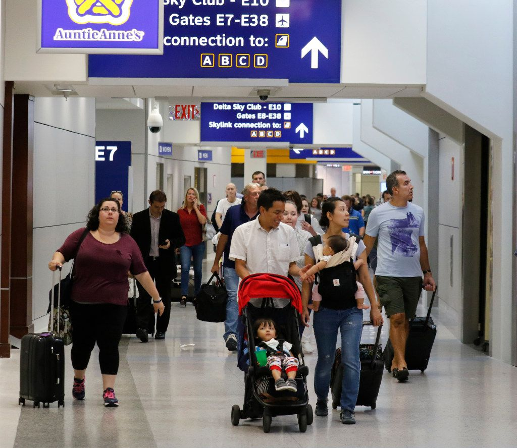 Travelers walk through the newly remolded Terminal E at Dallas Fort Worth International Airport on Wednesday, August 23, 2017. Today marks the second completed terminal in DFW's $2.7  billion terminal renewal and improvement program to renovate three of it's original terminal buildings. (David Woo/The Dallas Morning News)