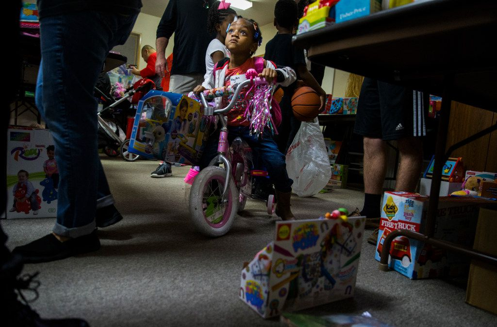 Kayden Eakles, 5, rides a bikes as she chooses toys during The Big Christmas Do-Over in Rowlett.