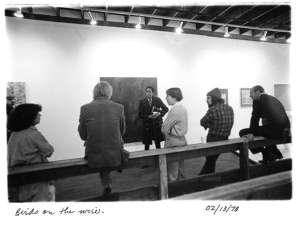 A group of gallery members leans and sits against a railing inside 500X Gallery in 1978, the year the gallery opened.