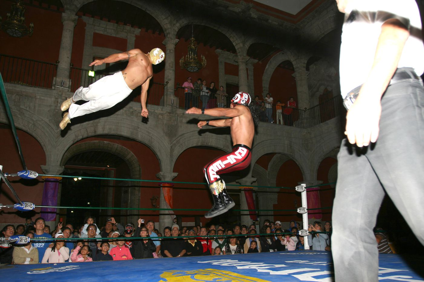 Shaun Leonardo, or El Conquistador de Nueva York (left), leaps from the top turnbuckle during a wrestling match. This photo appears in the new, glossy art magazine about wrestling culture, Orange Crush, a passion project edited by art adviser and fan Adam Abdalla.