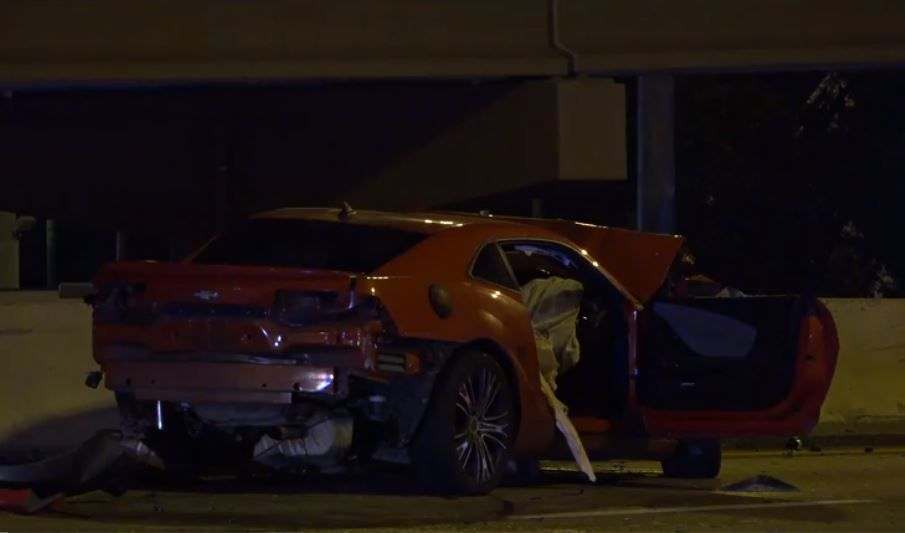 A wrecked Camaro lies along Interstate 35E near Royal Lane in northwest Dallas after it was involved in a multi-vehicle crash Friday morning.