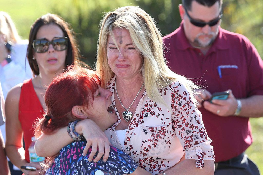 Parents wait for news after a reports of a shooting at Marjory Stoneman Douglas High School in Parkland, Fla., on Wednesday.