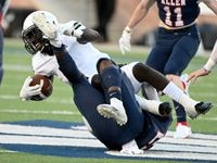 Plano East Ismail Mahdi, in white, is tackled by Allen's Michael Momoh in the first half during a high school football game between Plano East and Allen, Friday, Aug. 27, 2021, in Allen, Texas.