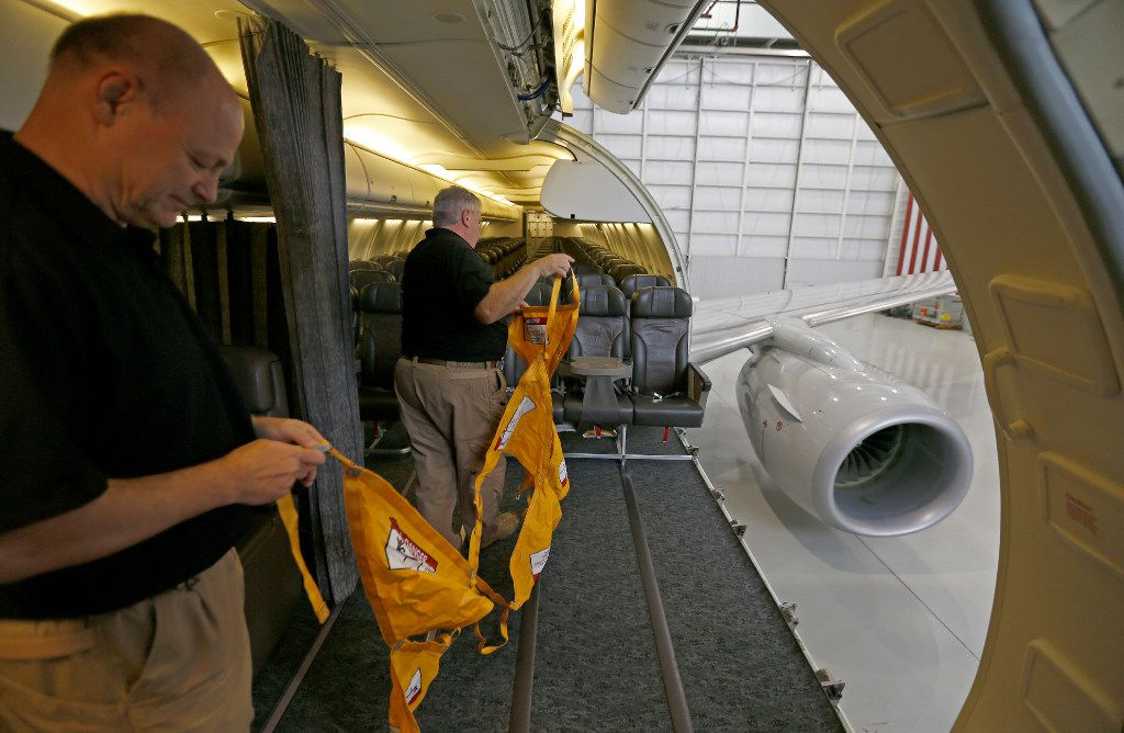 Rob Adsett (left), Director of Maintenance, and Butch Wunderlin, Flight Technician, prepares to install a safety net inside the B737-700 aircraft at Hillwood Airways Hangar at Fort Worth Alliance Airport in Fort Worth, Texas, Tuesday, Aug. 8, 2017. (Jae S. Lee/The Dallas Morning News)