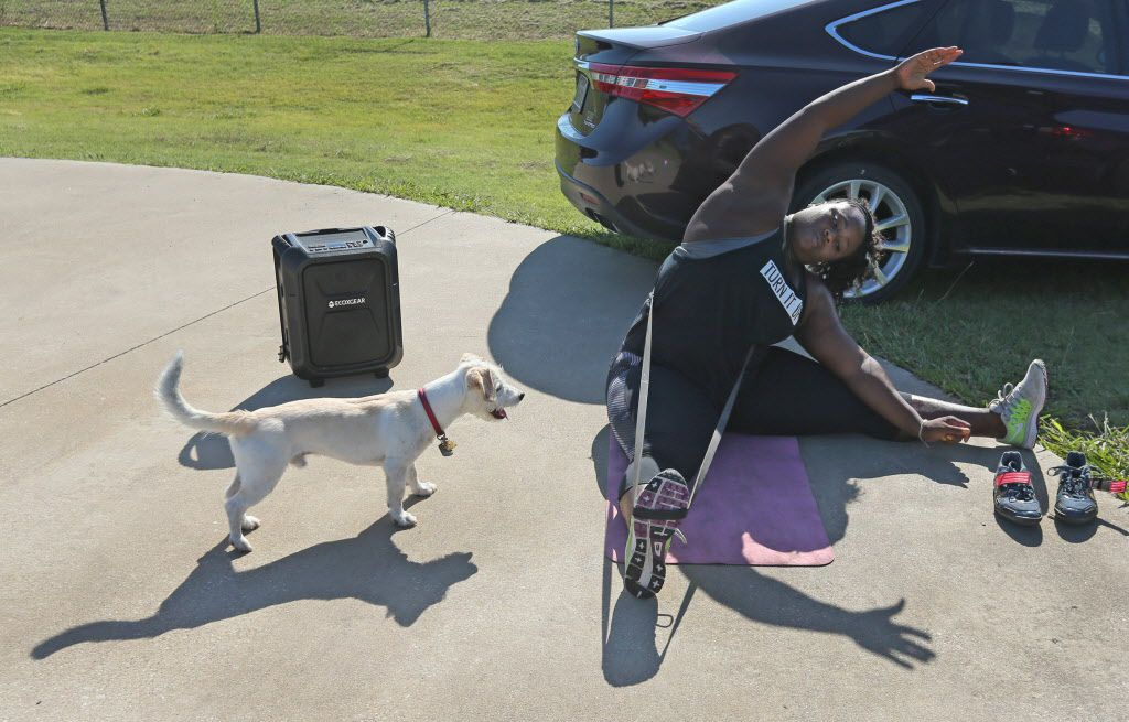 Olympian Michelle Carter warms up as her father's dog Rider watches before her workout at the Jesse Owens Complex in Dallas on Thursday, July 13, 2017.