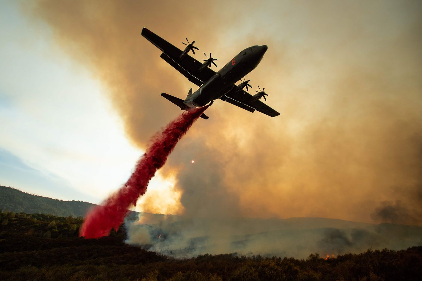 An air tanker drops retardant on the Ranch Fire, part of the Mendocino Complex Fire, burning along High Valley Rd near Clearlake Oaks, California, on August 5, 2018. Several thousand people have been evacuated as various fires swept across the state, although some have been given permission in recent days to return to their homes. / AFP PHOTO / NOAH BERGERNOAH BERGER/AFP/Getty Images