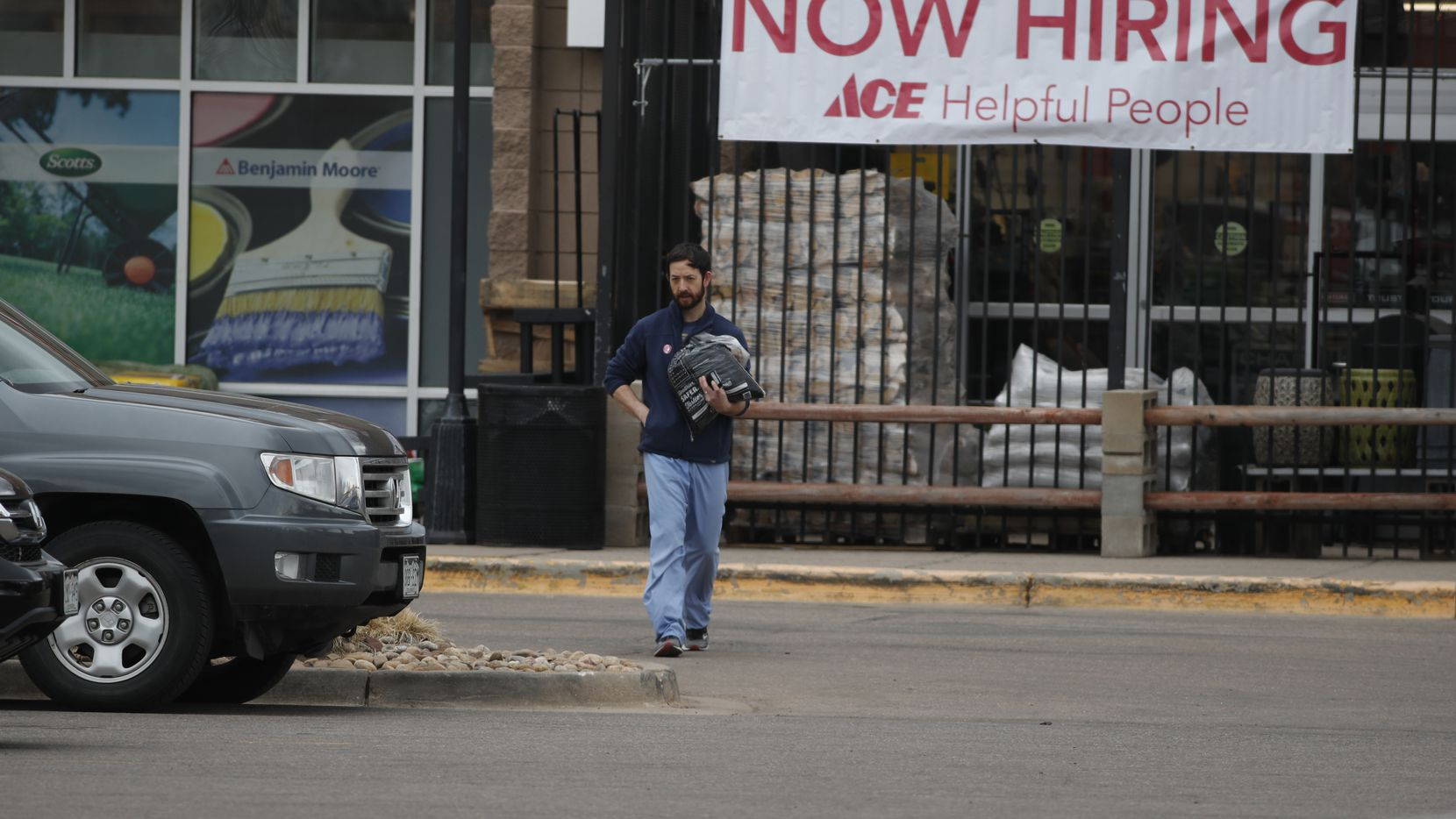A shopper heads out of an Ace Hardware store past a sign advertising for workers during a statewide stay-at-home order in an effort to reduce the spread of the new coronavirus Friday, March 27, 2020, in Denver.