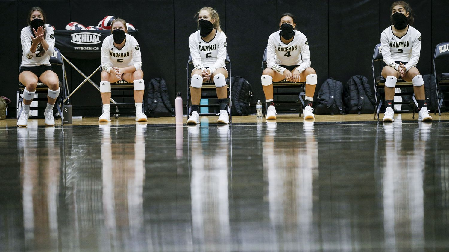 The Kaufman varsity volleyball reserve players wear masks while social distancing on the bench during a volleyball match against Lindale at Kaufman High School, Tuesday, August 11, 2020.