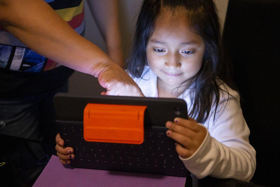 Adali Arriaza ayuda a su hija Daysha Cojulum, de 5 años, a subir sus tareas desde la mesa de la cocina en su hojgar en el noreoeste de Dallas.